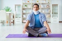 L'uomo con la lesione del collo che medita a casa su pavimento Immagini Stock Libere da Diritti