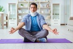 L'uomo con la lesione del collo che medita a casa su pavimento Immagini Stock