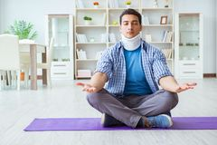L'uomo con la lesione del collo che medita a casa su pavimento Fotografia Stock Libera da Diritti