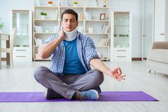 L'uomo con la lesione del collo che medita a casa su pavimento Immagine Stock Libera da Diritti