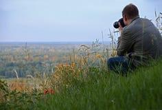 l'uomo con la macchina fotografica si siede su un'alta collina verde accanto ai fiori rossi del papavero immagini stock libere da diritti