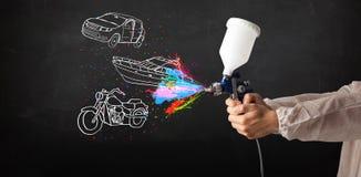 L'uomo con la pittura di spruzzo dell'aerografo con l'automobile, la barca ed il motociclo disegnano Fotografia Stock