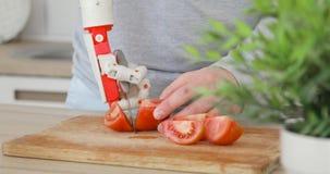 L'uomo con la protesi robot passa con il coltello su sta provando a tagliare il pomodoro sul bordo di legno Reinnervation del mus archivi video