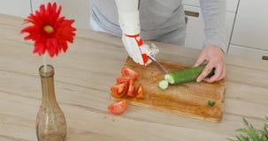 L'uomo con la protesi robot passa con il coltello su sta tagliando il cetriolo per insalata sul bordo di legno Reinnervation del  archivi video
