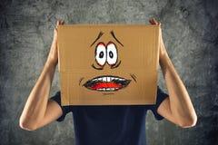 L'uomo con la scatola di cartone sulla suoi testa e sguardo terrorizzato skethed immagini stock libere da diritti