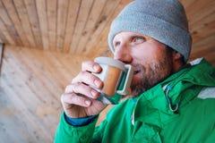 L'uomo con la tazza della bevanda calda riscalda sull'aria aperta dell'inverno Immagine Stock