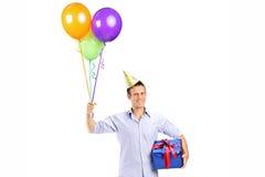 L'uomo con la tenuta del cappello del partito balloons e un presente Immagine Stock Libera da Diritti