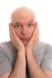 L'uomo con la testa calva ed il pollice su sta guardando ha stupito dentro al Ca Immagini Stock