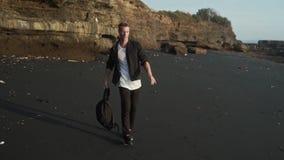 L'uomo con le passeggiate dello zaino lungo la spiaggia di sabbia nera, fa il trucco acrobatico Movimento lento, colpo di Steadic stock footage