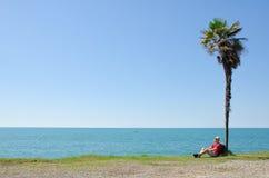 L'uomo con lo zaino si siede sotto una palma alta su fondo del mare e del cielo blu Immagini Stock