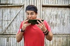 L'uomo con stoppia con espressione facciale divertente sta mangiando l'anguria immagine stock libera da diritti