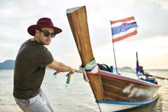 L'uomo con stoppia sta tirando la barca di legno dalla corda su acqua bassa fotografia stock libera da diritti