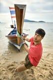 L'uomo con stoppia sta tirando la barca di legno dalla corda sulla spiaggia di sabbia immagini stock