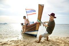 L'uomo con stoppia sta tirando la barca di legno con il tipo sulla spiaggia di sabbia fotografia stock libera da diritti