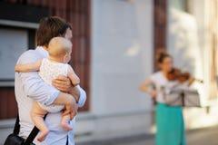 L'uomo con suo figlio ascolta fiddler Fotografie Stock Libere da Diritti