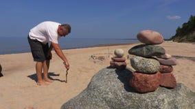 L'uomo con un albero nel tiraggio della sabbia firma