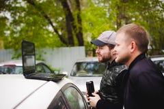 L'uomo con un computer portatile nel parcheggio nell'iarda vicino all'automobile sta facendo le manipolazioni con il sistema cybe Immagini Stock