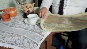 L'uomo con un legame svolge un rotolo e comincia esaminare la vecchia mappa archivi video