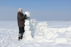 L'uomo con una barba in un cappuccio grigio che costruisce un iglù Fotografia Stock