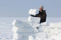 L'uomo con una barba in un cappuccio grigio che costruisce un iglù Immagini Stock
