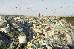 L'uomo con una borsa prende i rifiuti immagine stock