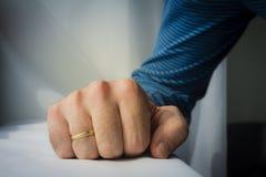L'uomo con una fede nuziale ha schiacciato la sua mano sul backgro bianco del panno Immagini Stock Libere da Diritti