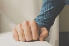 L'uomo con una fede nuziale ha schiacciato la sua mano sul backgro bianco del panno Immagini Stock