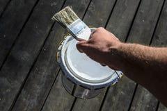 L'uomo con una forte mano porta una latta di pittura sopra il terrazzo e tiene una spazzola, la riparazione in una casa privata,  fotografia stock