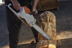L'uomo con una motosega crea una scultura fatta di legno fotografia stock