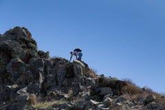 L'uomo con uno zaino scala sulla montagna piana per completare sopra Immagini Stock Libere da Diritti