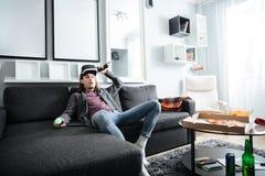 L'uomo concentrato che si siede a casa all'interno gioca Fotografia Stock