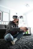 L'uomo concentrato che si siede a casa all'interno gioca Immagini Stock Libere da Diritti