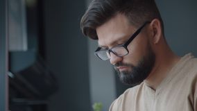 L'uomo concentrato legge le notizie o praticare il surfing su Internet in un caffè video d archivio