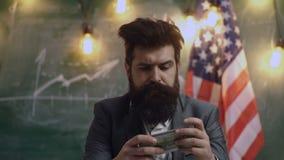 L'uomo concepito tiene i soldi contro lo sfondo della bandiera americana Concetti per lo sviluppo dell'affare video d archivio