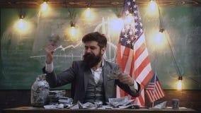 L'uomo concepito tiene i soldi contro lo sfondo della bandiera americana Concetti per lo sviluppo dell'affare archivi video