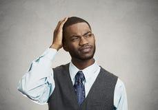 L'uomo confuso cerca su fondo grigio Fotografia Stock