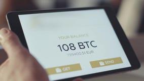 L'uomo controlla il conto sulla compressa azione Controllo dell'equilibrio del bitcoin sul conto stock footage
