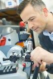 L'uomo controlla il lavoratore del tecnico alla macchina del metallo fotografia stock libera da diritti