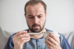 L'uomo controlla la temperatura corporea con un termometro a mercurio Tema delle malattie virali, influenza, freddo fotografia stock libera da diritti