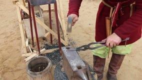 L'uomo in costume colpisce il metallo sull'incudine dal martello stock footage