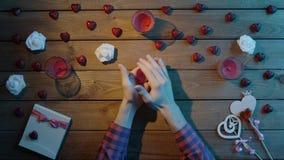 L'uomo creativo con cuore di carta si siede dalla tavola di legno, vista superiore video d archivio