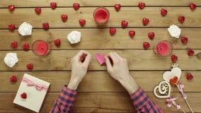 L'uomo creativo con cuore fatto a mano di carta si siede dalla tavola, vista superiore archivi video