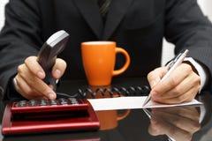 L'uomo d'affari è documento soddisfacente e calcolare con la cuffia avricolare Immagini Stock