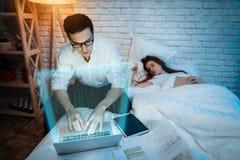 L'uomo d'affari adulto lavora alla notte a casa Riuscito commerciante che analizza i grafici delle paia di valuta fotografia stock