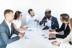 L'uomo d'affari africano che spiega le vendite rappresenta graficamente ai colleghi nella riunione Riassunto di progetto fotografie stock