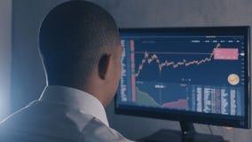 L'uomo d'affari afroamericano in camicia bianca analizza il mercato di vendite Il punto di vista posteriore dell'agente di cambio stock footage