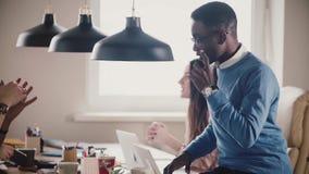 L'uomo d'affari afroamericano si siede sulla tavola dell'ufficio, giochi con pochi colloqui di calcio al primo piano del moviment archivi video