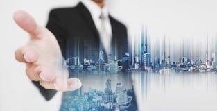 L'uomo d'affari allunga fuori la mano, con la città della doppia esposizione e la città futuristica dell'ologramma a disposizione Immagini Stock Libere da Diritti