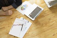 L'uomo d'affari analizza i dati dal grafico della relazione di attività Vista superiore del desktop funzionante di legno con labt Fotografia Stock Libera da Diritti