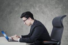 L'uomo d'affari arabo utilizza il computer portatile sullo scrittorio Fotografia Stock